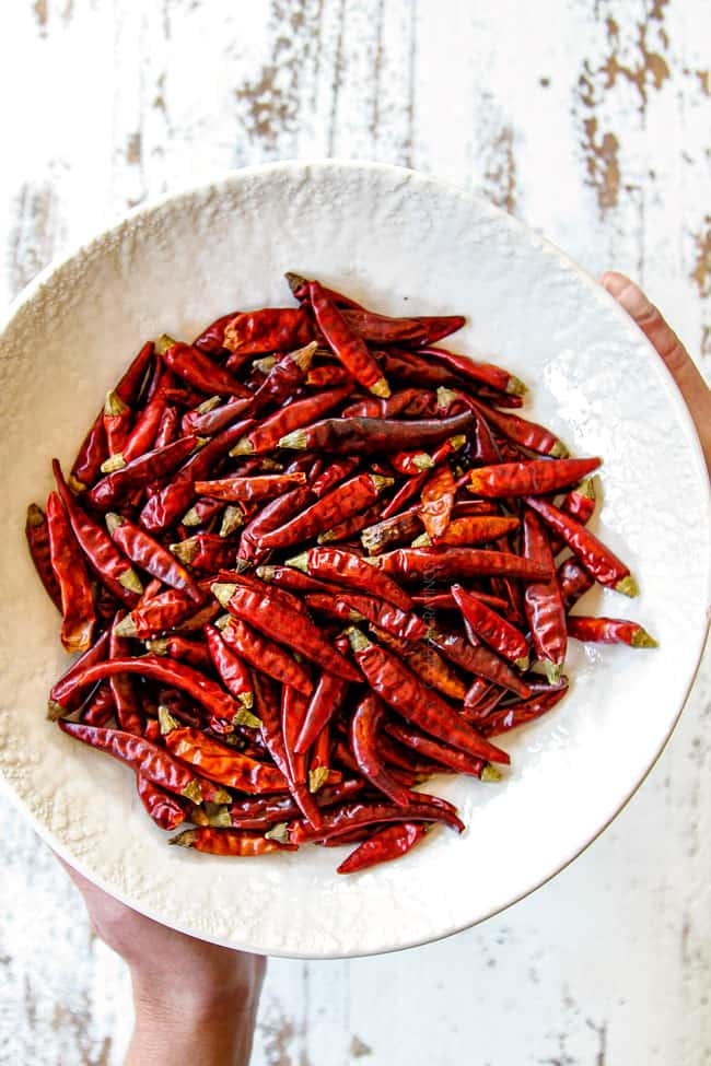showing what chilies to use in Szechuan Chicken by holding a bowl of Thai chilies