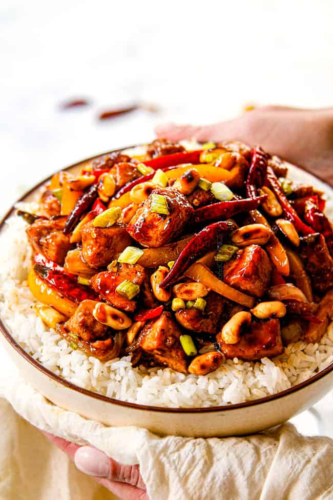 two hands holding a bowl of chicken szechuan style