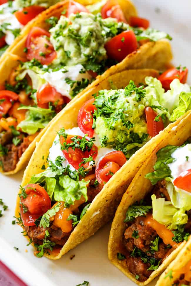 up close of showing what toppings for beef taco recipe by adding lettuce to tacos