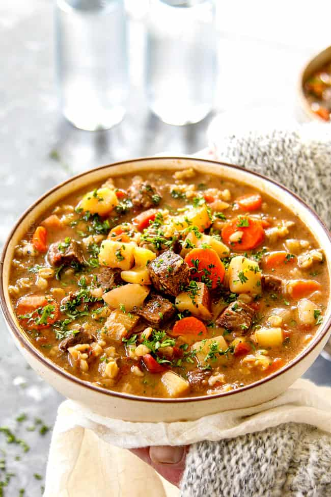 showing how to serve beef and barley soup recipes by garnishing with parsley
