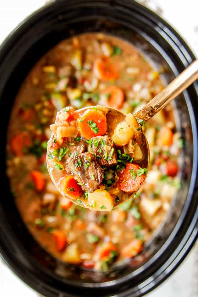 showing how to make crockpot beef and barley soup by adding beef broth to adjust consistency