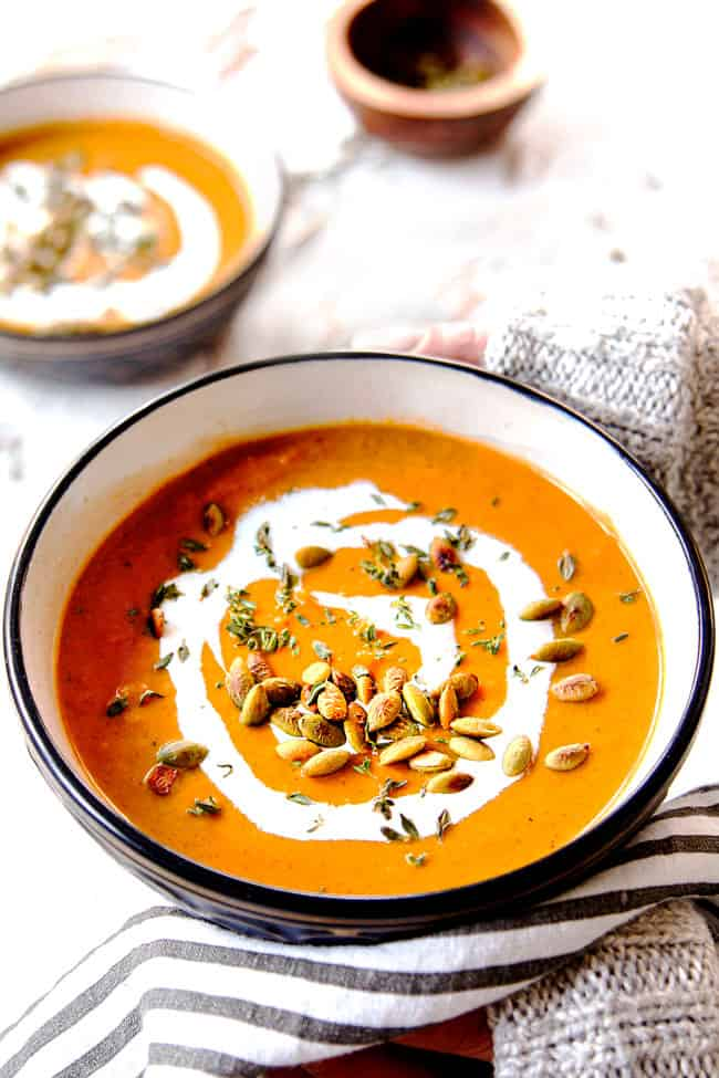 two hand holding a bowl of creamy butternut squash soup recipe