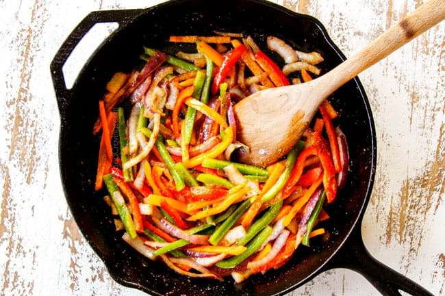 showing how to make Cajun shrimp pasta by cooking bell peppers and onions in a cast iron skillet