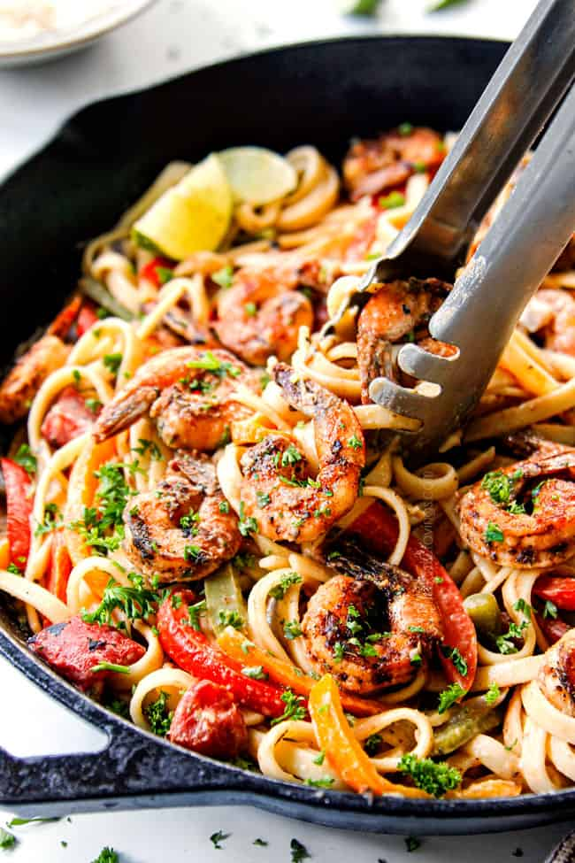 showing how to serve Cajun Shrimp Pasta recipe by garnishing with parsley and freshly grated Parmesan
