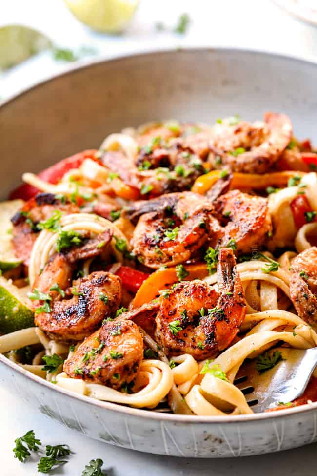 up close of a white bowl of Alfredo Cajun Shrimp Pasta recipe with shrimp, bell peppers, red onion, parsley and Parmesan