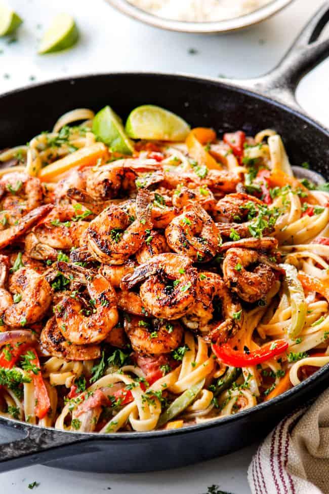 showing how to make creamy Cajun Shrimp Pasta recipe by adding blackened shrimp to pasta