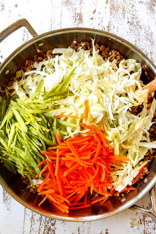 showing how to make Egg Roll in a Bowl by adding cabbage, carrots, snow peas to ground pork