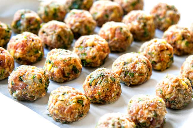 showing how to make Italian Meatball Soup by rolling ground beef, pork and herbs into meatballs and lining in rows on parchment paper