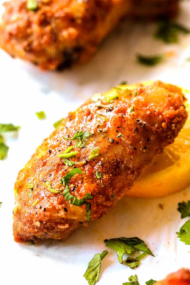 up close showing how to serve baked lemon pepper chicken wings by serving with ranch dip