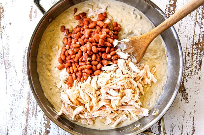 showing how to make green chicken enchilada casserole by stirring beans and chicken into enchilada sauce