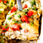 up close of serving chicken enchilada casserole recipe with a slice on a silver spatula