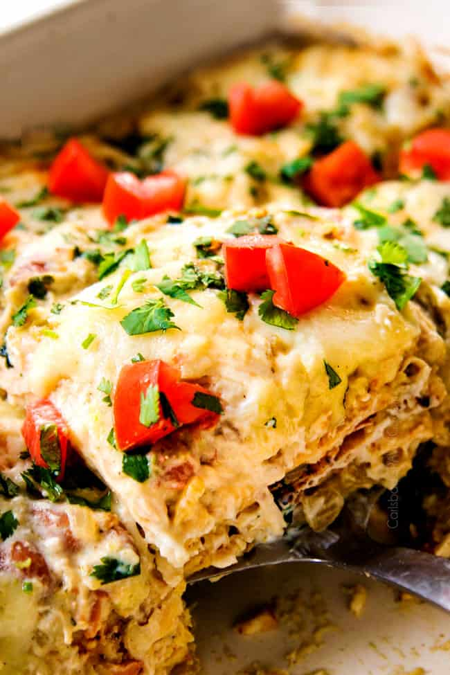 up close of a slice of green chicken enchilada casserole recipe topped with tomatoes and cilantro in a baking dish
