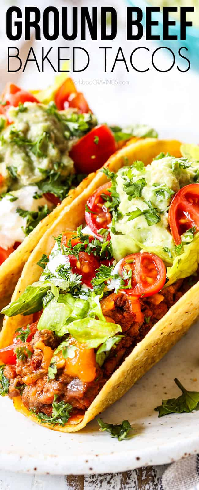 up close showing how to serve ground beef tacos by topping with lettuce, sour cream and tomatoes