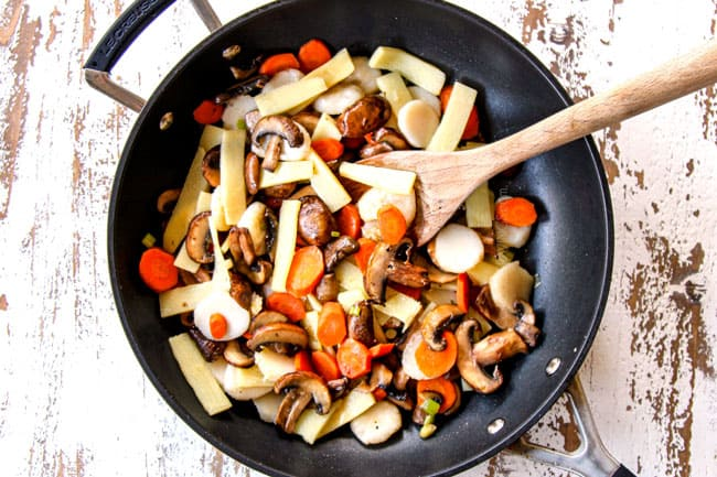 showing how to make Moo Goo Gai Pan by stir frying water chestnuts, bamboo shoots, garlic, ginger and green onions