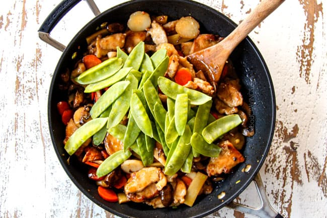 showing how to make Moo Goo Gai Pan by adding snow peas to the sauce and simmering for one minute