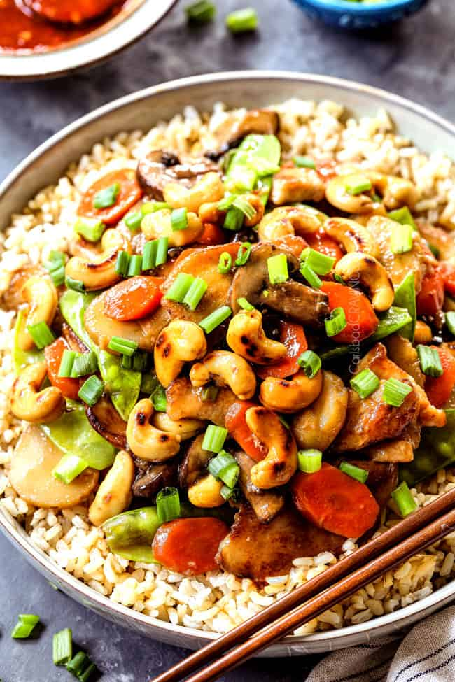 up close of serving Moo Goo Gai Pan in a bowl with rice garnished by green onions with chopsticks