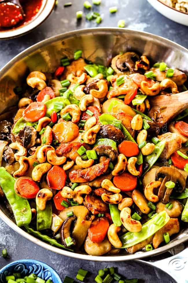 showing how to make authentic Moo Goo Gai Pan recipe by stir frying thinly sliced chicken, mushrooms, carrots, snow peas, water chestnuts and bamboo shoots together
