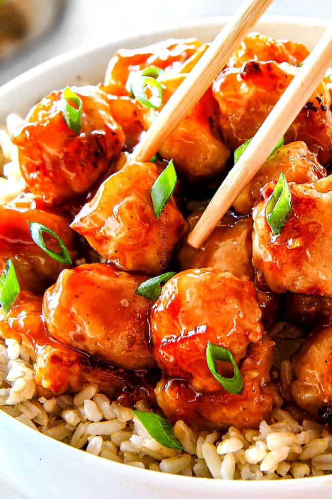 showing how to eat homemade orange chicken recipe by picking up a piece of chicken with chopsticks