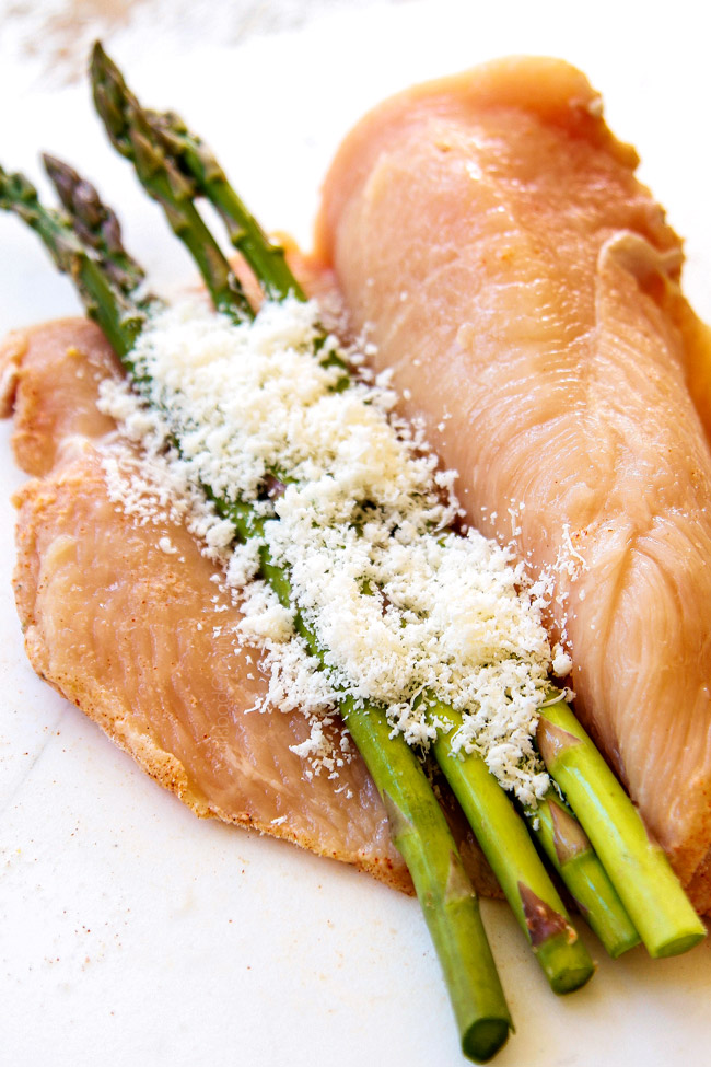 showing how to make chicken piccata recipe by adding Parmesan and asparagus to chicken