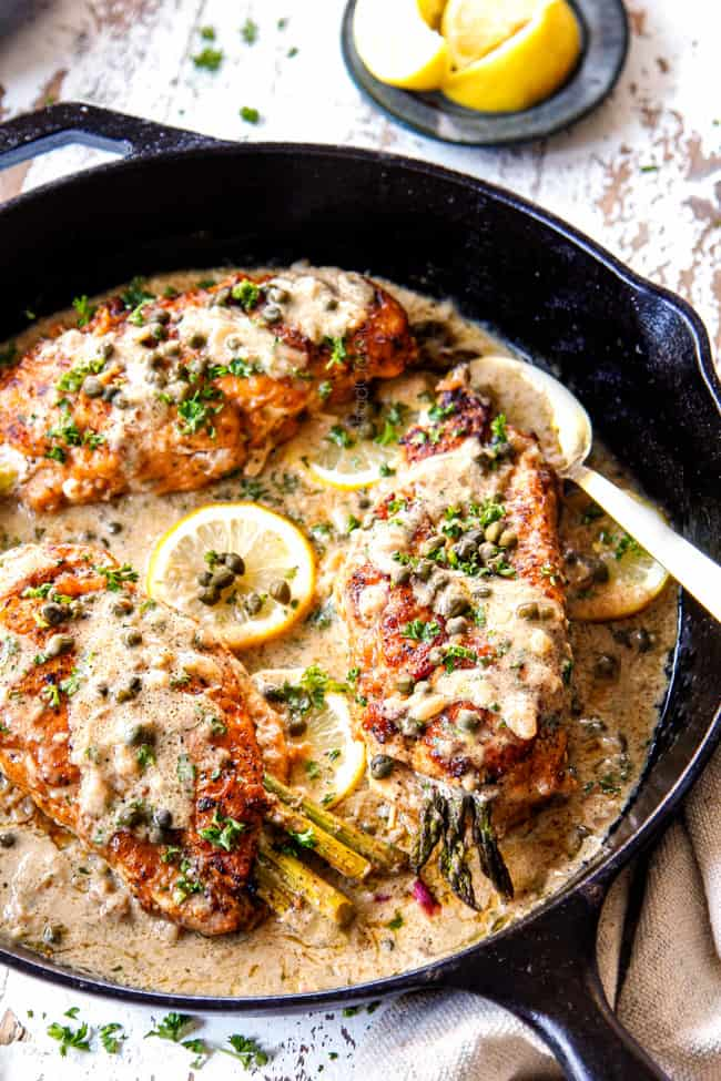 showing how to serve Chicken Piccata by spooning sauce over the chicken
