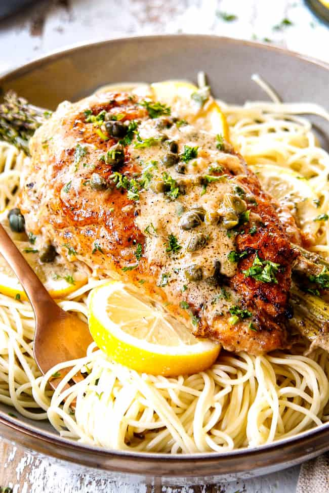 up close of a piece of chicken piccata on a bowl of linguine pasta showing what to serve with chicken piccata