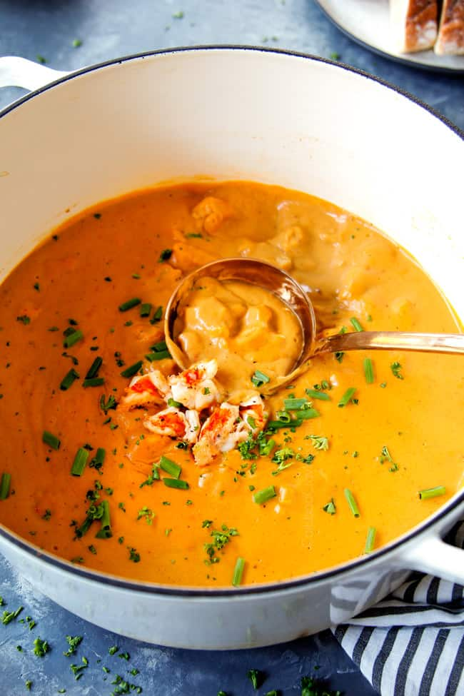 showing how to serve easy lobster bisque recipe with a ladle scooping up the soup