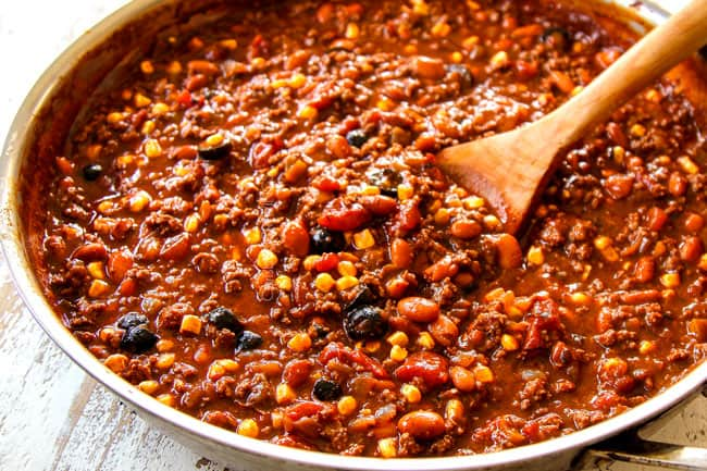 showing how to make Mexican Lasagna recipe by warming beans,corn and olives in a large skillet with the beef and sauce