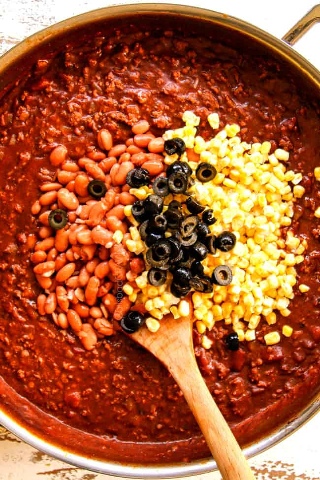 showing how to make Mexican Lasagna recipe by adding pinto beans, black olives and corn to saucy beef mixture