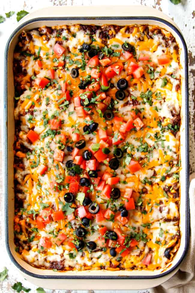 showing how to garnish Mexican Lasagna recipe with a top view of the lasagna with tomatoes, olives and cilantro