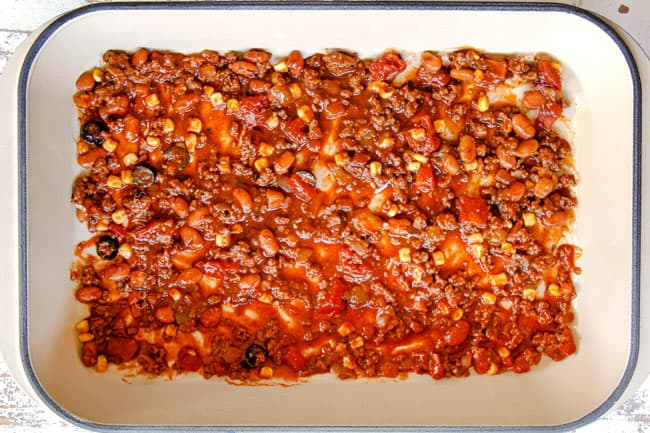 showing how to make Mexican Lasagna by layering the bottom of a 9x13 baking dish with 1 ½ cups of meat sauce