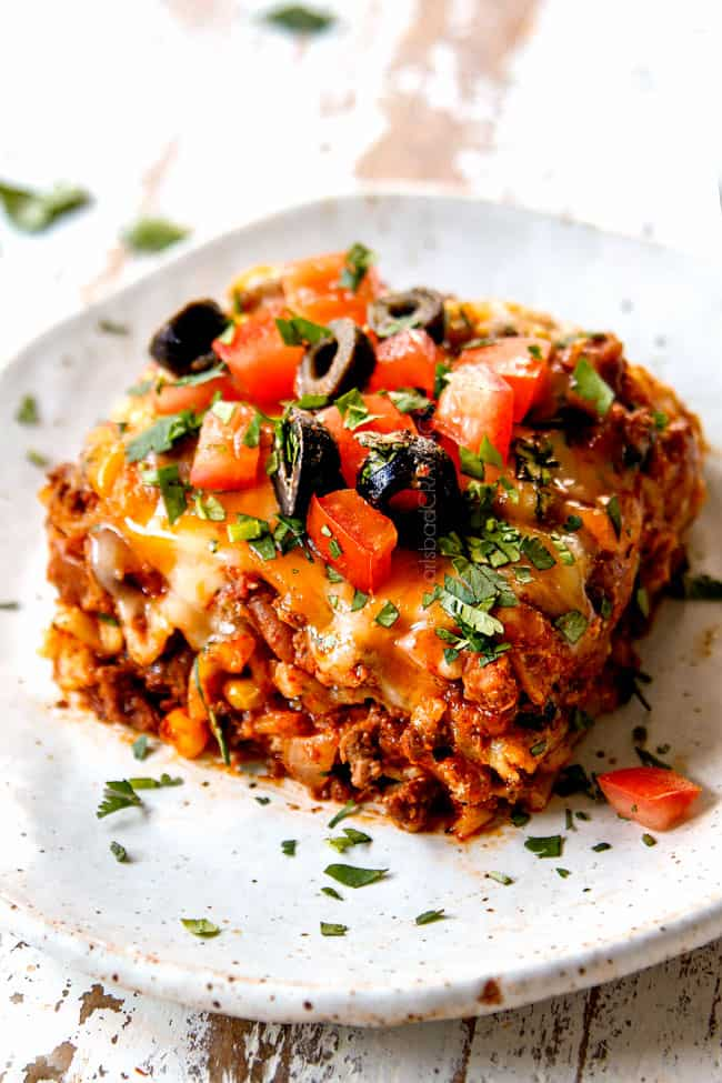 showing how to top Mexican Lasagna recipe by adding sour cream, olives, tomatoes and cilantro to a piece of lasagna on a plate