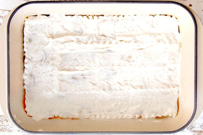 showing how to make Mexican Lasagna recipe by layering lasagna noodles with creamy sour cream layer