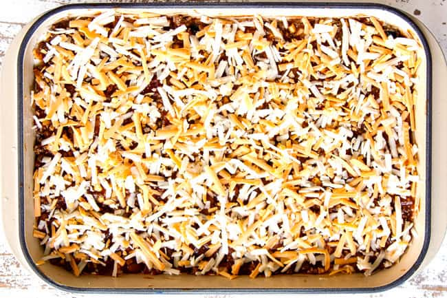 showing how to make Mexican Lasagna recipe by finishing layers with one layer of meat sauce and shredded cheeee