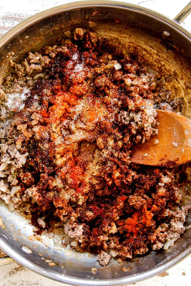 showing how to make Mexican Lasagna recipe by cooking ground beef in a large skillet until browned then adding chili powder, ground cumin, smoked paprika