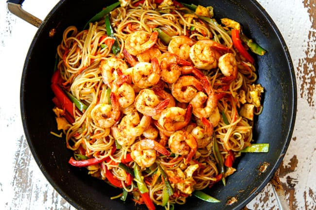 showing how to make Singapore Noodles by adding the cooked shrimp back to the skillet along with the eggs and tossing to combine