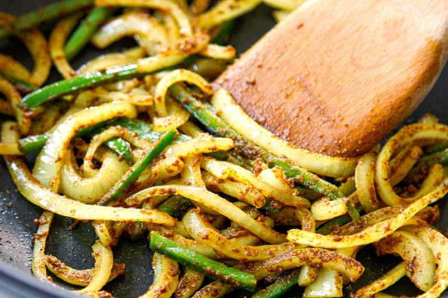 showing how to make Singapore Noodles recipe by stir frying onions, jalapenos and curry powder
