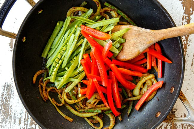showing how to make Singapore Style Noodles by stir frying red bell peppers and snow peas