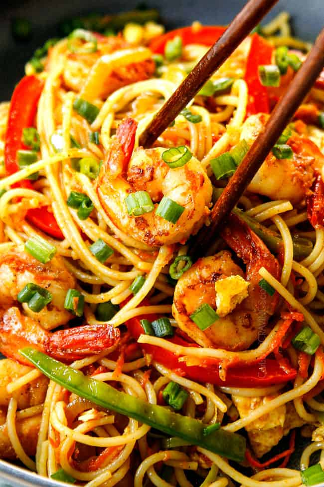 up close of showing how to eat Singapore Noodles recipe by picking up a piece of shrimp and noodles with chopsticks
