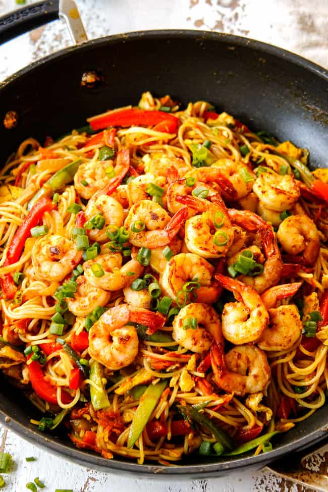 showing how to make Singapore Style Noodles by adding cooked shrimp to the top of stir fried noodles