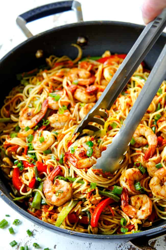 showing how to serve Singapore Noodles recipe by using tongs to pick up noodles
