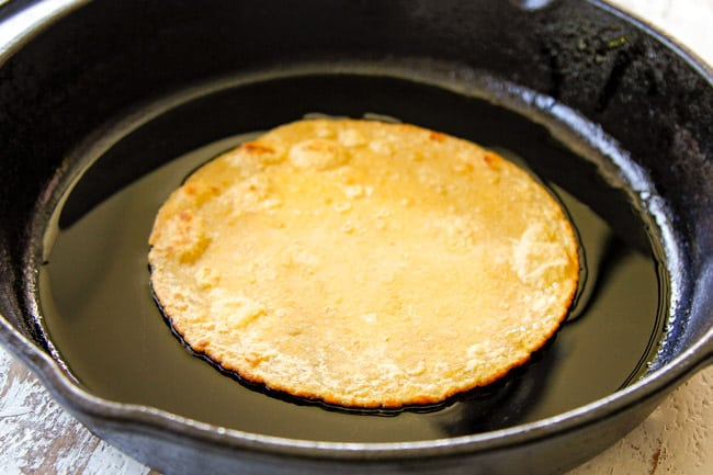 showing how to make easy chicken enchiladas by flash frying corn tortillas in a cast iron skillet