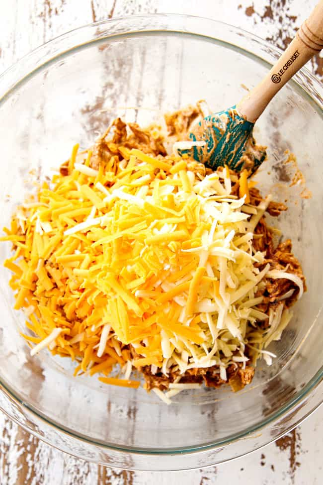 showing how to make chicken enchiladas by adding Monterrey Jack cheese and shredded cheddar cheese to the chicken filling in a glass bowl