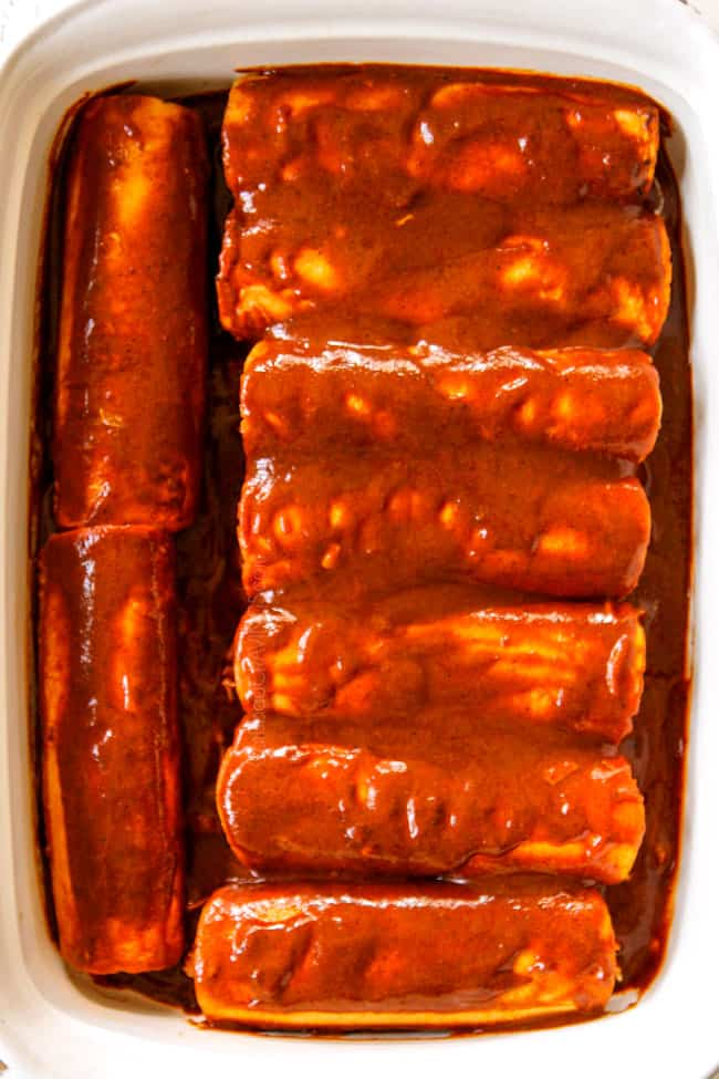 showing how to make easy chicken enchiladas by placing rolled tortillas with filling seam side down in a 9x13 baking dish