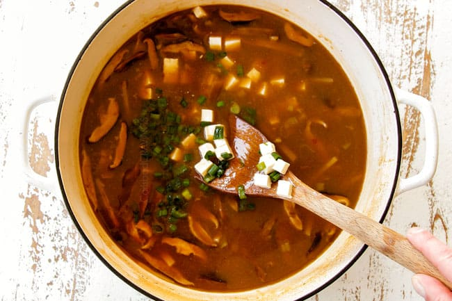showing how to make hot and sour soup recipe by adding tofu and green onions and cornstarch slurry