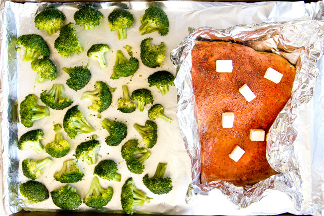 showing how to make salmon pasta by placing salmon and broccoli next to each other on a baking sheet