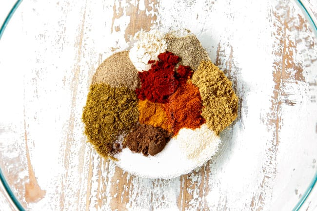showing to make chicken shawarma into bowls by adding cumin, coriander, paprika, turmeric, cayenne, onion powder, garlic powder, salt and pepper to a bowl