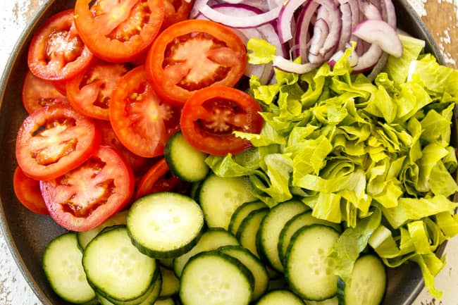 showing to make shawarma by chopping tomatoes, lettuce, red onions and cucumbers