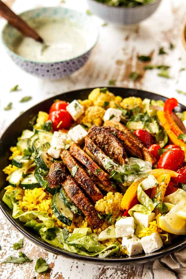 showing to make chicken shawarma into bowls by adding chicken, roasted cauliflower, bell peppers, tomatoes and zucchini to a black bowl with rice and lettuce