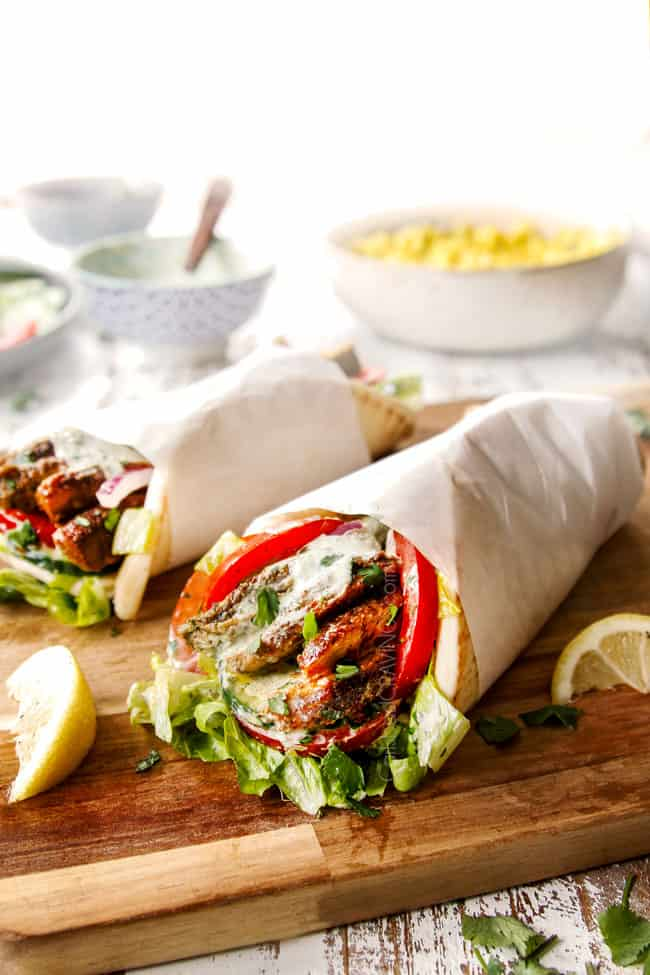 showing how to serve shawarma by drizzling chicken shawarma wraps with yogurt sauce