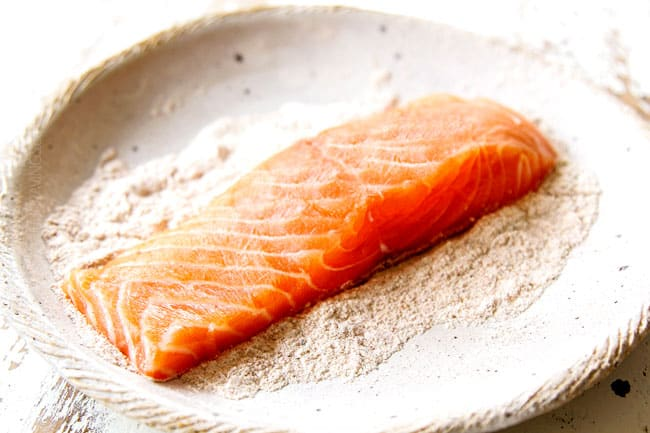 showing how to make lemon salmon and asparagus by adding salmon to shallow bowl with flour to dredge